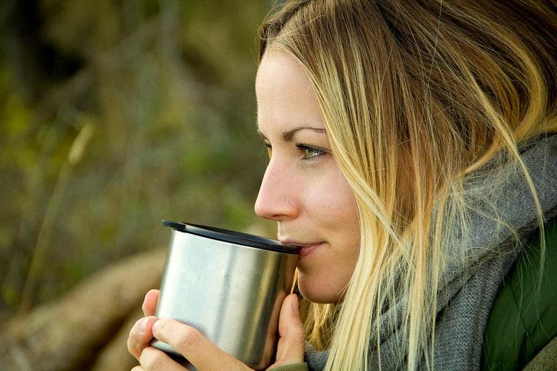 Молодая девушка пьет чай
