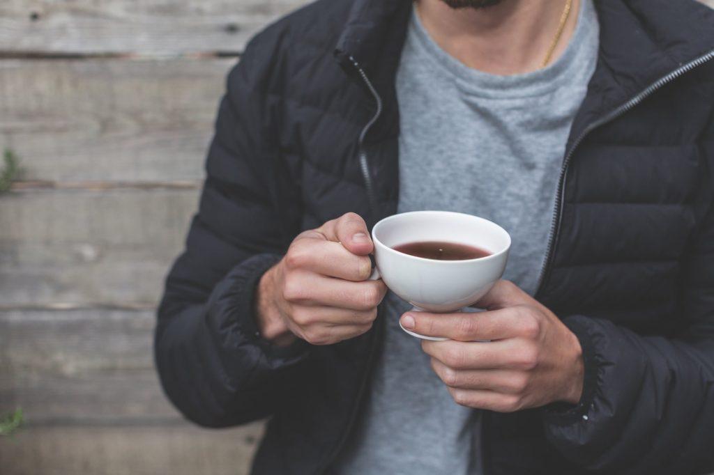 Мужчина держит в руках кружку с чаем